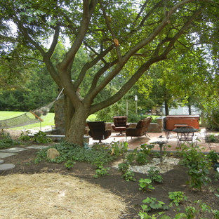 Design ideas for a mid-sized traditional drought-tolerant and shade backyard stone landscaping in Philadelphia with a fireplace for spring.