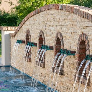 Réalisation d'un très grand jardin avec une terrasse en bois ou composite arrière tradition l'été avec une cascade et une exposition partiellement ombragée.