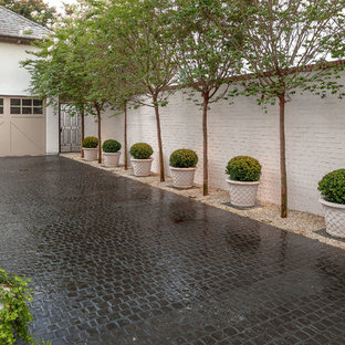 This is an example of a mid-sized traditional partial sun stone driveway in Houston.