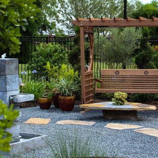 Diseño de jardín francés, de estilo americano, extra grande, en patio trasero, con fuente, exposición total al sol y gravilla