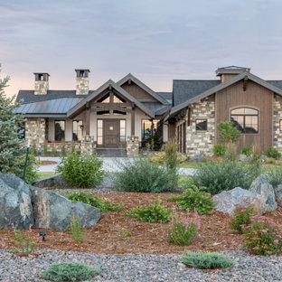 Immagine di un ampio vialetto d'ingresso stile americano esposto in pieno sole davanti casa con sassi e rocce e pacciame