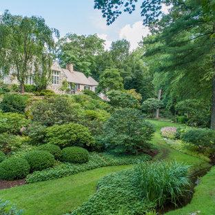 Aménagement d'un grand jardin à la française classique l'été avec un massif de fleurs, une exposition ensoleillée et une pente, une colline ou un talus.
