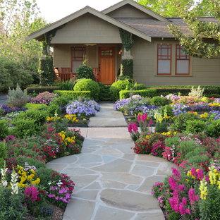 Bild på en mellanstor amerikansk trädgård framför huset och blomsterrabatt på sommaren, med naturstensplattor