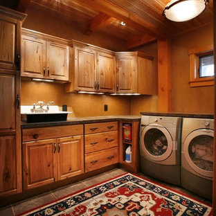 Dedicated laundry room - large rustic porcelain tile dedicated laundry room idea in Other with raised-panel cabinets, medium tone wood cabinets, granite countertops, brown walls, a side-by-side washer/dryer and a drop-in sink