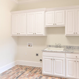 Inspiration for a large timeless brick floor dedicated laundry room remodel in New Orleans with a drop-in sink, raised-panel cabinets, white cabinets, granite countertops, beige walls and a side-by-side washer/dryer
