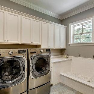 Foto på en vintage tvättstuga, med luckor med infälld panel, vita skåp, grå väggar och en tvättmaskin och torktumlare bredvid varandra