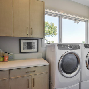 Example of a trendy light wood floor dedicated laundry room design in San Francisco with light wood cabinets, gray walls and white countertops