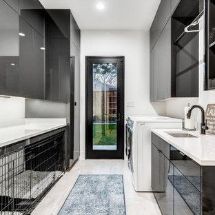 Idee per una grande sala lavanderia minimal con ante lisce, ante nere, pareti bianche, pavimento in gres porcellanato, lavatrice e asciugatrice affiancate, pavimento nero e top bianco