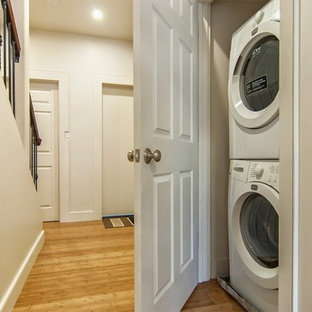 Inspiration for a small single-wall bamboo floor laundry closet remodel in San Francisco with a stacked washer/dryer and beige walls