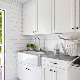 Inspiration for a transitional gray floor and shiplap wall laundry room remodel in San Francisco with a farmhouse sink, recessed-panel cabinets, white cabinets, white walls and gray countertops