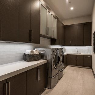 Modern inredning av en mellanstor vita l-formad vitt tvättstuga enbart för tvätt, med en undermonterad diskho, släta luckor, bruna skåp, bänkskiva i kvarts, vita väggar, klinkergolv i porslin, en tvättmaskin och torktumlare bredvid varandra och beiget golv