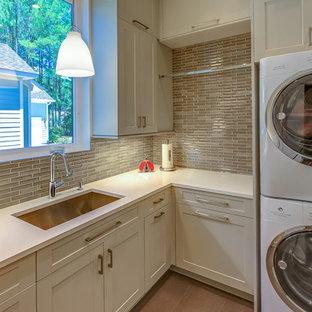 Foto di una sala lavanderia minimal di medie dimensioni con lavello a vasca singola, pavimento in gres porcellanato, lavatrice e asciugatrice a colonna, ante in stile shaker, ante bianche, top in quarzo composito e pavimento marrone