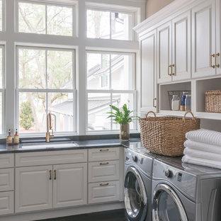 Bild på en stor vintage l-formad tvättstuga, med en undermonterad diskho, luckor med upphöjd panel, vita skåp, bruna väggar, mörkt trägolv, en tvättmaskin och torktumlare bredvid varandra och svart golv