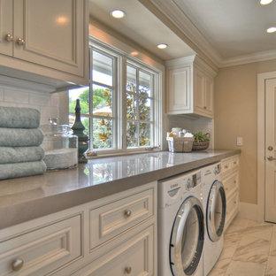 Ispirazione per una lavanderia costiera con ante bianche, pavimento bianco e top grigio