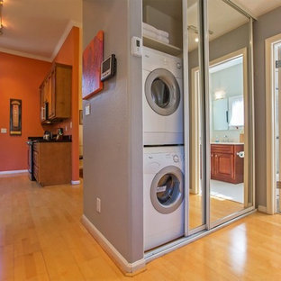 Ispirazione per un piccolo ripostiglio-lavanderia minimal con lavatrice e asciugatrice a colonna, pareti grigie e pavimento in bambù
