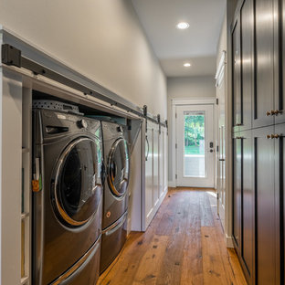 Small cottage single-wall medium tone wood floor and brown floor laundry closet photo in Seattle with shaker cabinets, black cabinets, gray walls and a side-by-side washer/dryer