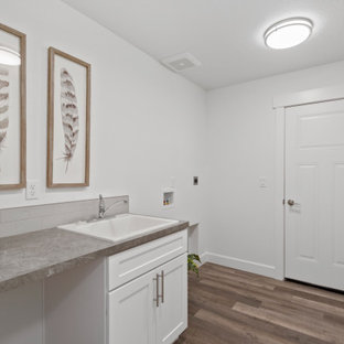 This is an example of a mid-sized single-wall utility room with shaker cabinets, white cabinets, laminate benchtops, a side-by-side washer and dryer, grey benchtop, an utility sink, multi-coloured splashback, mosaic tile splashback, white walls, laminate floors and grey floor.