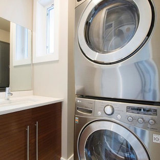 Utility room - mid-sized single-wall utility room idea in Calgary with a drop-in sink, flat-panel cabinets, medium tone wood cabinets, solid surface countertops, white walls and a stacked washer/dryer
