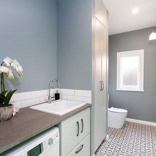 Esempio di una piccola lavanderia tradizionale con ante con bugna sagomata, ante grigie, top in quarzo composito, pavimento in legno verniciato, pavimento rosso, top grigio e lavello da incasso
