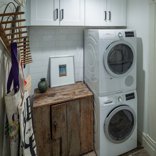 Example of a small cottage brown floor laundry closet design in Denver with shaker cabinets, white cabinets, wood countertops, white walls and a stacked washer/dryer