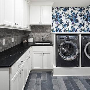 Inredning av en stor svarta l-formad svart tvättstuga enbart för tvätt, med en undermonterad diskho, släta luckor, vita skåp, bänkskiva i täljsten, flerfärgade väggar, klinkergolv i keramik, en tvättmaskin och torktumlare bredvid varandra och grått golv