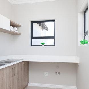 Exempel på en liten modern vita l-formad vitt tvättstuga enbart för tvätt, med en dubbel diskho, släta luckor, skåp i mellenmörkt trä, bänkskiva i kvarts, grå väggar, klinkergolv i porslin, en tvättmaskin och torktumlare bredvid varandra och grått golv