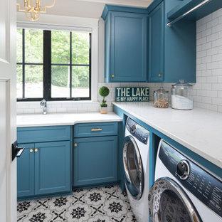 Foto di una sala lavanderia stile marino di medie dimensioni con lavello sottopiano, ante blu, top in superficie solida, pavimento con piastrelle in ceramica, pavimento multicolore, top bianco, ante in stile shaker, pareti grigie e lavatrice e asciugatrice affiancate