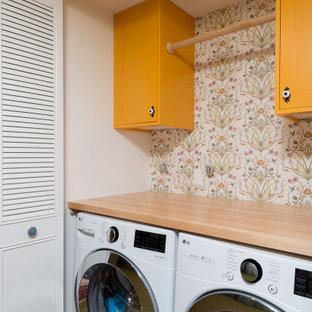 Idéer för en liten shabby chic-inspirerad bruna linjär liten tvättstuga, med skåp i shakerstil, gula skåp, träbänkskiva, vita väggar, laminatgolv, en tvättmaskin och torktumlare bredvid varandra och brunt golv