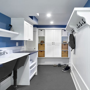 Mid-sized arts and crafts galley utility room in Vancouver with a farmhouse sink, beaded inset cabinets, white cabinets, laminate benchtops, white splashback, blue walls, a stacked washer and dryer, grey floor, blue benchtop and decorative wall panelling.