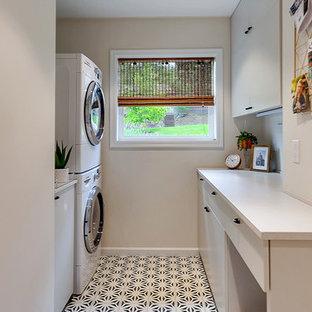 Esempio di una piccola lavanderia multiuso moderna con ante lisce, ante grigie, top in quarzo composito, pareti grigie, pavimento con piastrelle in ceramica, lavatrice e asciugatrice a colonna, pavimento blu e top grigio