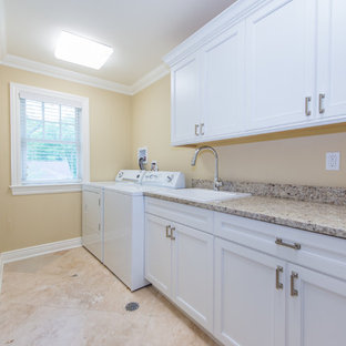 Inspiration for a large traditional galley separated utility room in New York with a belfast sink, white cabinets, granite worktops, beige walls, a side by side washer and dryer, travertine flooring and beige floors.
