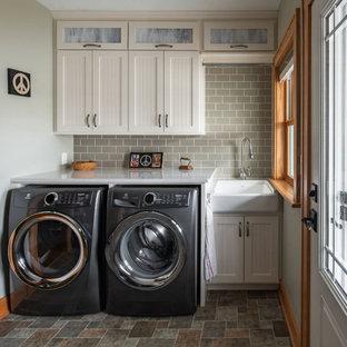 Klassisk inredning av en mellanstor vita linjär vitt tvättstuga enbart för tvätt, med en rustik diskho, luckor med infälld panel, vita skåp, bänkskiva i kvarts, gröna väggar, vinylgolv, en tvättmaskin och torktumlare bredvid varandra och flerfärgat golv