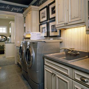 Inredning av en klassisk mellanstor linjär tvättstuga enbart för tvätt, med en nedsänkt diskho, en tvättmaskin och torktumlare bredvid varandra, grått golv, luckor med upphöjd panel, skåp i slitet trä, bänkskiva i betong, klinkergolv i keramik och svarta väggar