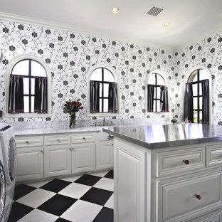Idee per un'ampia sala lavanderia tradizionale con ante bianche, lavello sottopiano, ante con bugna sagomata, top in acciaio inossidabile, pareti bianche, pavimento con piastrelle in ceramica, lavatrice e asciugatrice affiancate, pavimento multicolore e top grigio