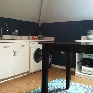 Bild på ett mellanstort vintage grovkök, med en enkel diskho, vita skåp, laminatbänkskiva, blå väggar, korkgolv och en tvättmaskin och torktumlare bredvid varandra