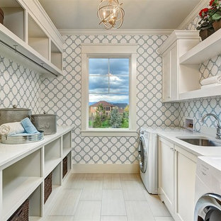 This is an example of a large transitional galley dedicated laundry room in Boise with an undermount sink, shaker cabinets, white cabinets, multi-coloured walls, quartz benchtops, porcelain floors, a side-by-side washer and dryer, grey floor and white benchtop.