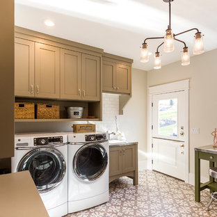 Example of a large arts and crafts galley ceramic tile utility room design in Salt Lake City with a drop-in sink, raised-panel cabinets, brown cabinets, stainless steel countertops, white walls and a side-by-side washer/dryer