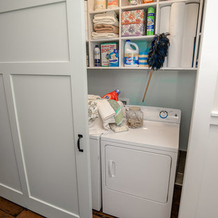 Small arts and crafts single-wall laundry cupboard in Other with open cabinets, white cabinets, white walls, medium hardwood floors and a side-by-side washer and dryer.