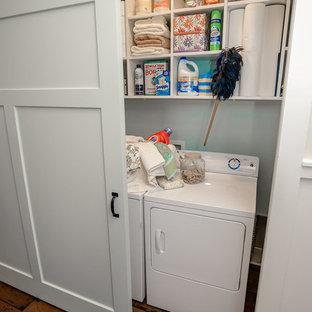 Idéer för små amerikanska linjära små tvättstugor, med öppna hyllor, vita skåp, vita väggar, mellanmörkt trägolv och en tvättmaskin och torktumlare bredvid varandra