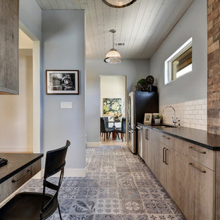 Multifunktionaler, Zweizeiliger, Großer Industrial Hauswirtschaftsraum mit Unterbauwaschbecken, flächenbündigen Schrankfronten, Granit-Arbeitsplatte, blauer Wandfarbe, Porzellan-Bodenfliesen, Waschmaschine und Trockner nebeneinander und grauen Schränken in Austin