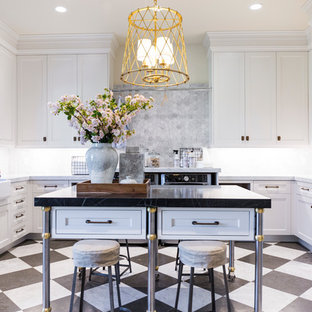 Large traditional u-shaped laundry room in Salt Lake City with a farmhouse sink, shaker cabinets, white cabinets, grey splashback, beige walls, marble benchtops, marble floors, a side-by-side washer and dryer, multi-coloured floor and black benchtop.