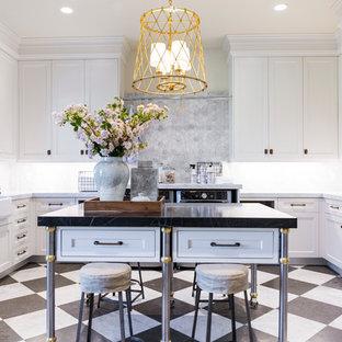 Exempel på en stor klassisk svarta u-formad svart tvättstuga, med en rustik diskho, skåp i shakerstil, vita skåp, grått stänkskydd, beige väggar, marmorbänkskiva, marmorgolv, en tvättmaskin och torktumlare bredvid varandra och flerfärgat golv