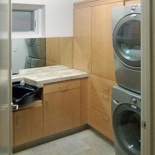 Foto di una grande lavanderia multiuso moderna con ante lisce, ante in legno chiaro, top piastrellato, pareti bianche, pavimento in gres porcellanato e lavatrice e asciugatrice a colonna