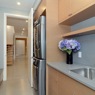 Inspiration for a mid-sized scandinavian galley utility room in Vancouver with an undermount sink, flat-panel cabinets, light wood cabinets, quartz benchtops, grey walls, concrete floors and a stacked washer and dryer.