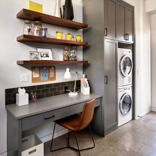 Example of a large trendy porcelain floor utility room design in Portland with shaker cabinets, gray cabinets, concrete countertops, white walls and a stacked washer/dryer