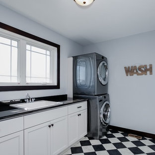 This is an example of a large traditional galley separated utility room in Minneapolis with a single-bowl sink, shaker cabinets, white cabinets, composite countertops, lino flooring, a stacked washer and dryer, white walls, brown floors and black worktops.