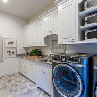 Bild på ett stort rustikt grovkök, med en undermonterad diskho, skåp i shakerstil, vita skåp, granitbänkskiva, vita väggar, klinkergolv i keramik och en tvättmaskin och torktumlare bredvid varandra