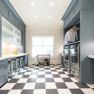 Utility room - huge transitional galley multicolored floor utility room idea in Salt Lake City with a farmhouse sink, a side-by-side washer/dryer, shaker cabinets, marble countertops, white walls, white countertops and blue cabinets
