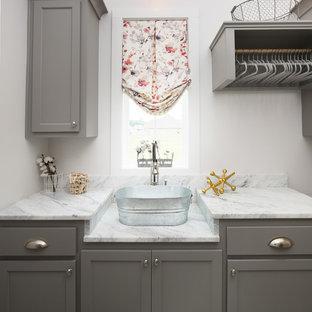 Exempel på en liten klassisk grå grått tvättstuga, med en enkel diskho, luckor med infälld panel och marmorbänkskiva