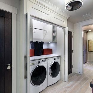 Réalisation d'une petite buanderie linéaire minimaliste avec un placard, un placard sans porte, des portes de placard blanches, un plan de travail en marbre, un mur blanc, un sol en bois clair, des machines côte à côte et un sol marron.